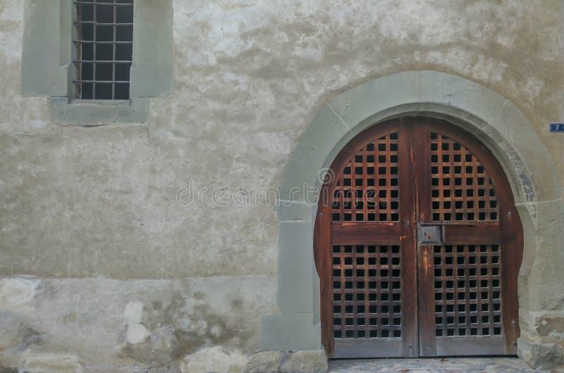 Een oud houten gesloten deur en een venster met gebarsten muur in straten van Lohara-dorp in Ludhiana, Punjab stock afbeelding