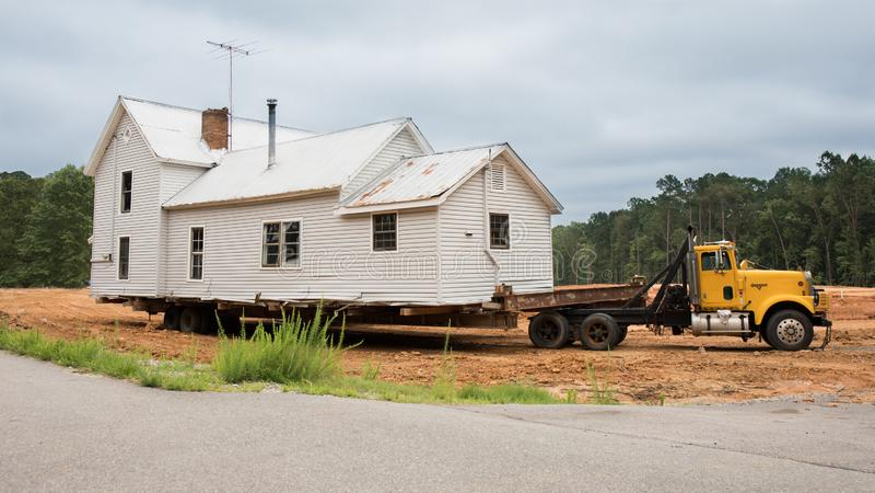Een oud huis klaar om achter een vlakke bedvrachtwagen worden bewogen royalty-vrije stock foto