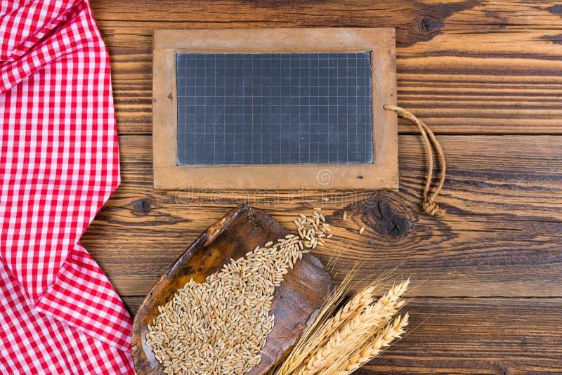 Een oud leibord, een zeer oude bloemlepel met graankorrels en korreloren royalty-vrije stock foto