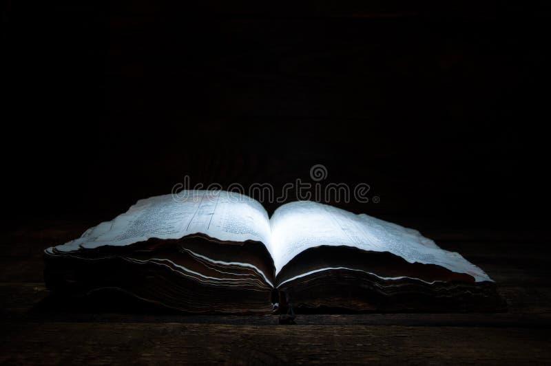 Een oud open boek ligt op een houten lijst in dark Een licht glanst hierboven op het boek van Heilige bijbel royalty-vrije stock afbeeldingen