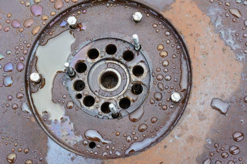 Een oud, roestig, nat die wiel met verse regendruppels in openlucht wordt behandeld Roest op een metaaloppervlakte Achtergrond Te royalty-vrije stock foto