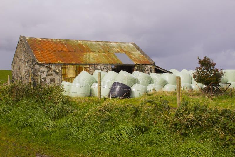 Een oud steenplattelandshuisje met het roesten plooide ijzerdak in Noord-Ierland dat voor het gebruik van de landbouwbedrijfopsla stock foto's