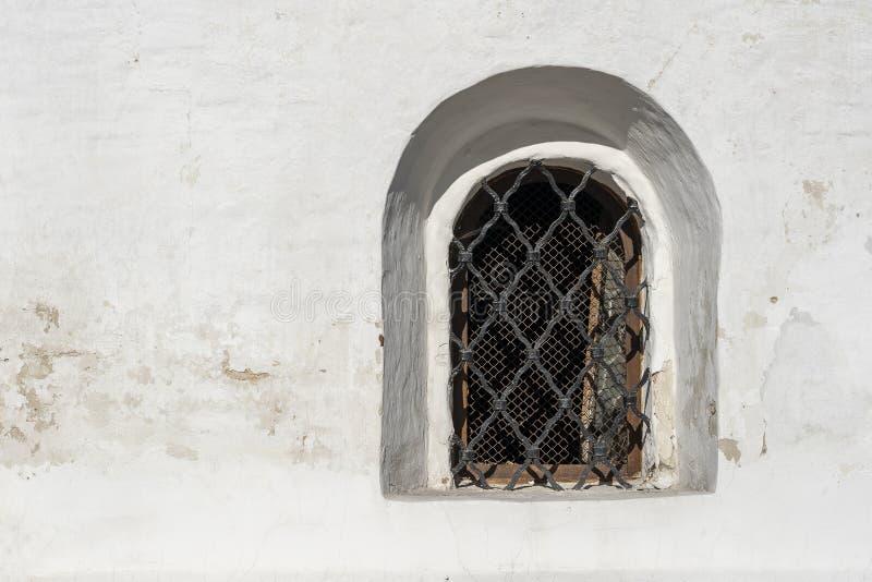 Een oud venster in de witte muur Rooster op het venster in de oude stijl Ouderwets architectuurconcept royalty-vrije stock afbeeldingen
