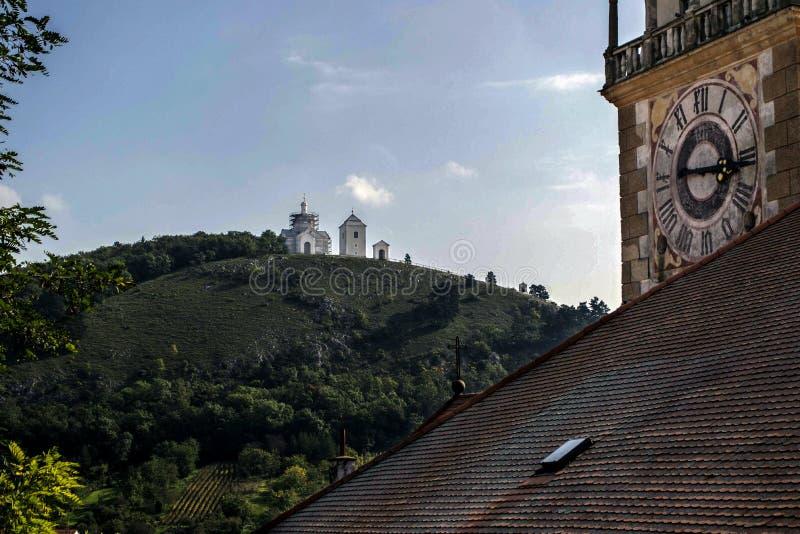 Een oude astronomische klok die de tegenovergestelde heuvel met een witte kapel overzien royalty-vrije stock afbeelding