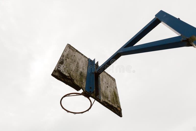 Een oude basketbalring met een witte houten plaat waar de verf weg en vast aan een blauwe staalpool op een witte achtergrond pelt stock afbeelding