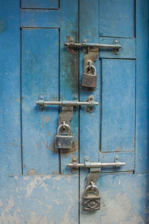 Een oude blauwe houten deur met drie hangsloten bouten op de deur stock fotografie