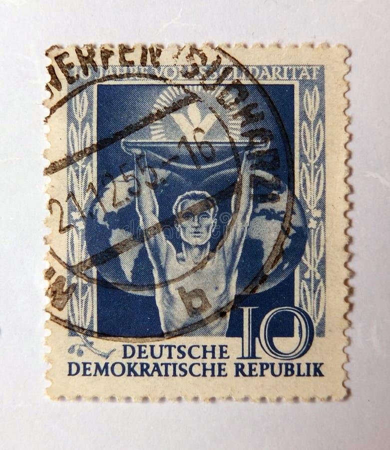 Een oude blauwe Oostduitse postzegel met een beeld van een mens die solidariteit achter een bol van de wereld afschilderen stock foto's
