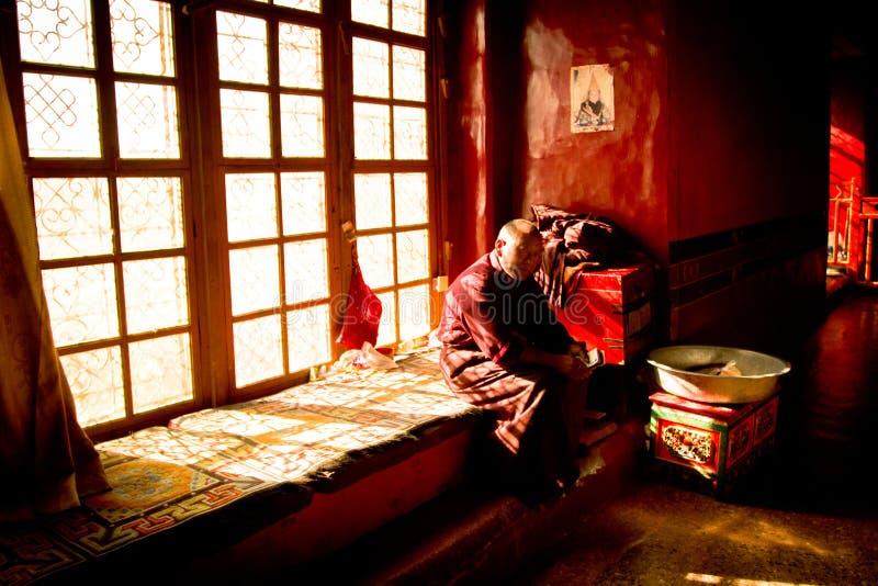 Een oude Boeddhistische monnikszitting in het venster Lhasa Tibet stock foto