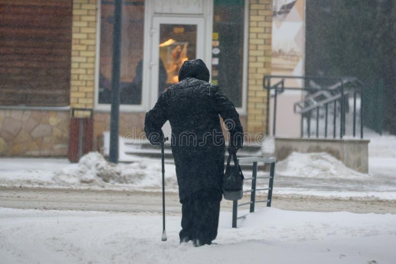 Een oude dame die met stok, tijdens sneeuwval lopen stock afbeelding