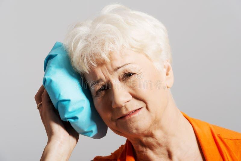 Een oude dame met ijszak door haar hoofd. stock afbeelding