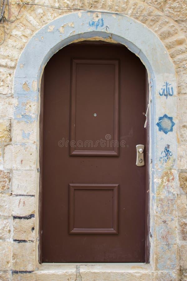 Een oude deur op een oud gebouw in de ommuurde stad van Jeruzalem stock foto's
