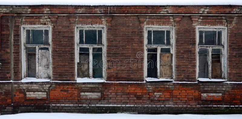 Een oude die bakstenen muur van een flatgebouw met heel wat op vensters zonder glas wordt ingescheept royalty-vrije stock fotografie