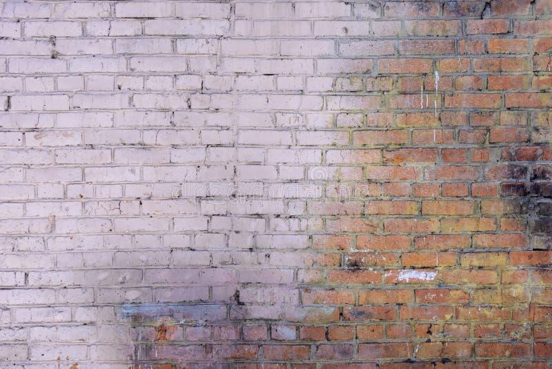 Een oude die bakstenen muur van rode bakstenen wordt gemaakt Een deel van de muur is geschilderd met bleek - roze verf Lege achte stock fotografie