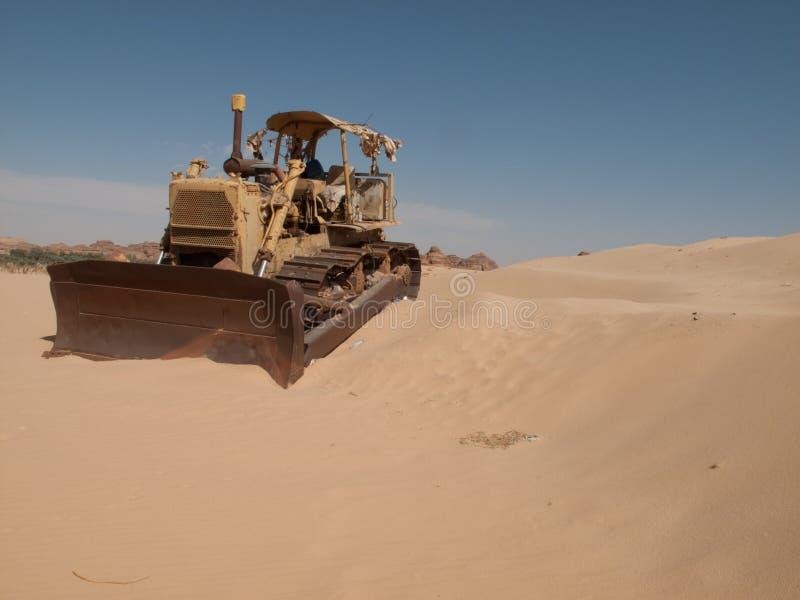 Een oude die bulldozer in het midden van de woestijn in Saudi-Arabië wordt verlaten stock afbeeldingen
