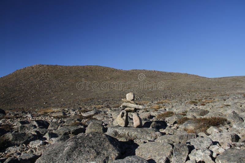 Een oude die Inuit inukshuk inuksuk dichtbij Qikiqtarjuaq als deel van oriëntatiepunten op een wandelingssleep wordt gevestigd, B stock afbeelding
