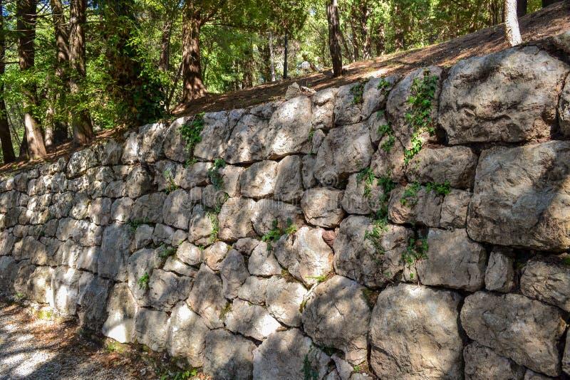 Een oude die steenmuur van ruwe steen wordt gemaakt Een oude versterkte muuromheining met een patroon van groen gras en mos stock foto
