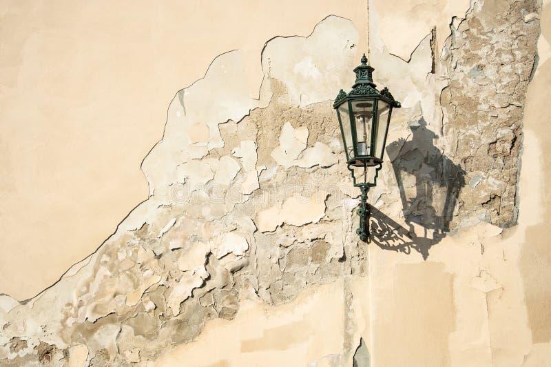 Een oude donkergroene squiggly lantaarn die een wolk over een grungy huismuur gieten in Prag royalty-vrije stock fotografie