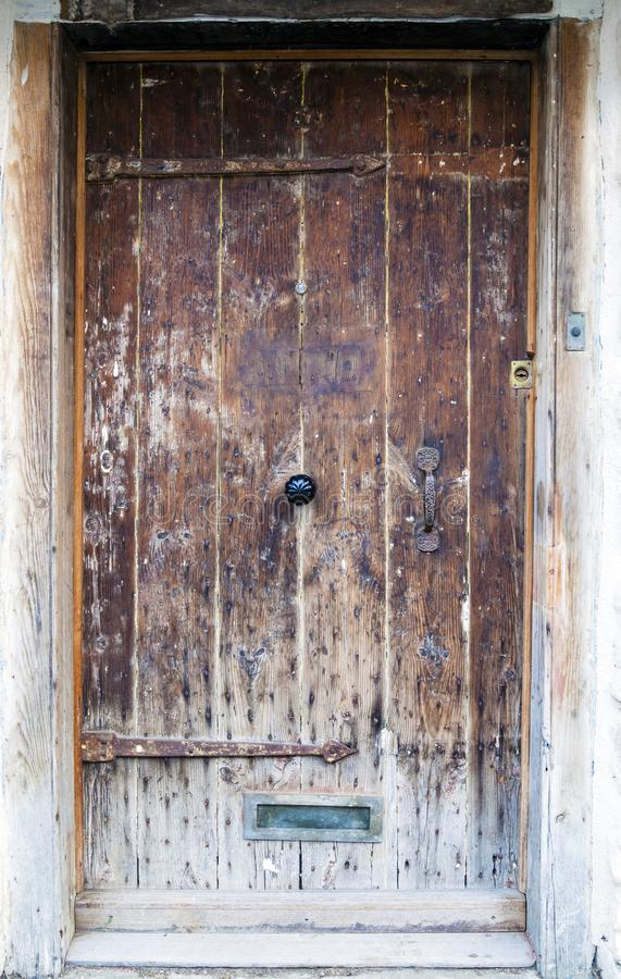 Een oude eiken houtdeur met overladen metaalhandvat stock foto's