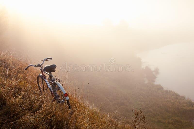 Een oude fiets vroeg in de ochtend in platteland en landschapsmist royalty-vrije stock foto