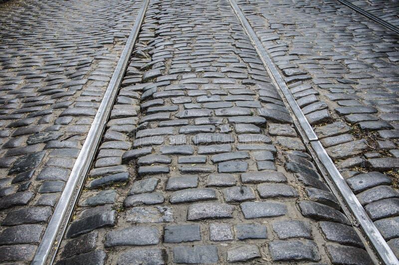 Een oude, gebroken die weg, van granietsteen wordt gemaakt met tramsporen Achtergrondsteen royalty-vrije stock afbeeldingen