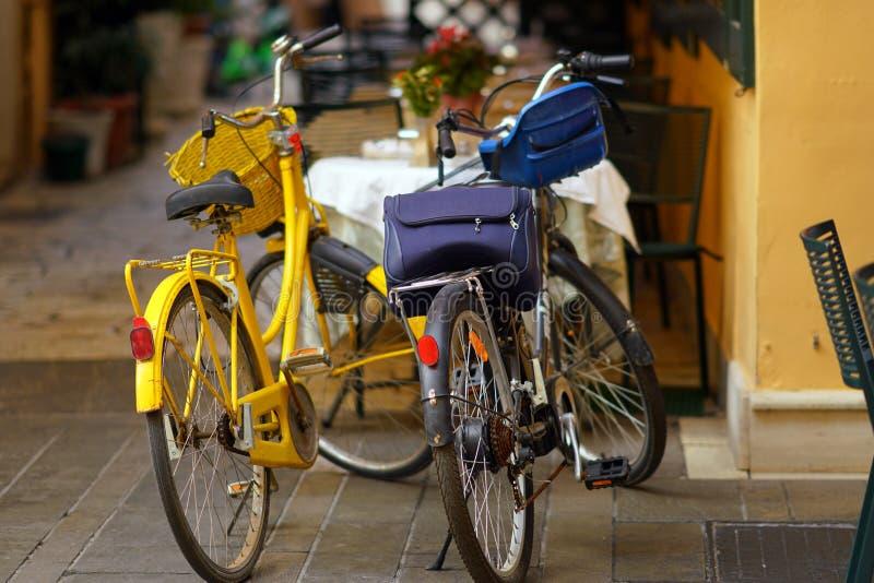 Een oude gele fiets en een moderne zwarte elektrische die fiets in een smalle straat van Korfu wordt geparkeerd stock foto's