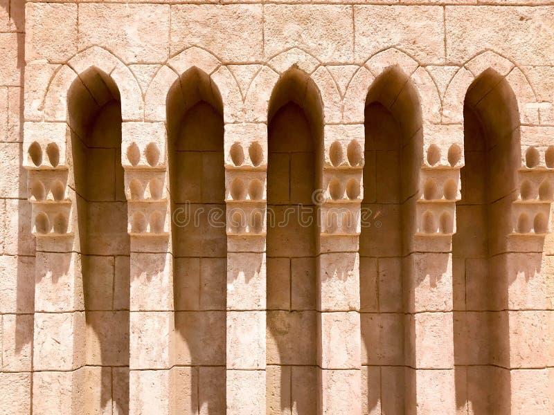 Een oude oude gele steen sterke muur met bogen in patronen en kolommen in een Arabisch Moslim Islamitisch warm tropisch land in royalty-vrije stock afbeelding