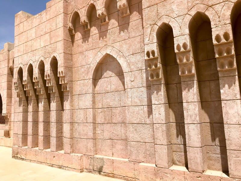 Een oude oude gele steen sterke muur met bogen in patronen en kolommen in een Arabisch Moslim Islamitisch warm tropisch land in royalty-vrije stock fotografie