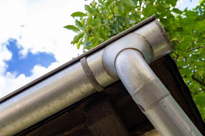 Een oude goot in een losgemaakt huis Regenwaterdrainage van het dak stock fotografie