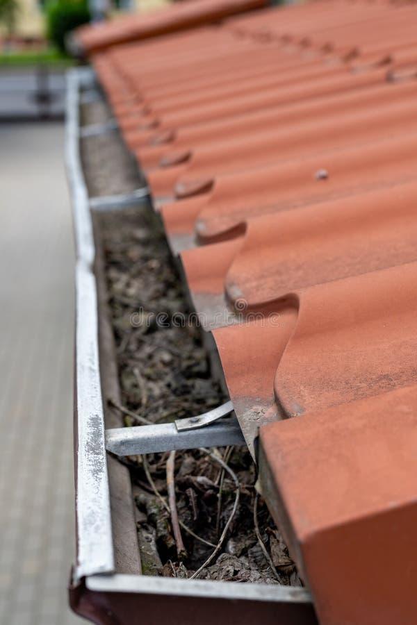 Een oude goot in een losgemaakt huis Regenwaterdrainage van het dak stock foto's