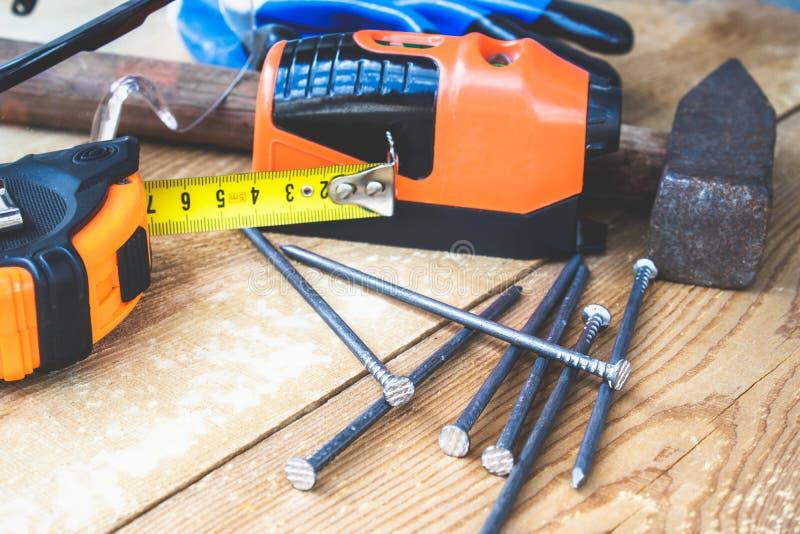 Een oude hamer met spijkers en een gele heerser van roulette dichtbij glazen voor de ogenbescherming en een laserniveau op een bo stock foto