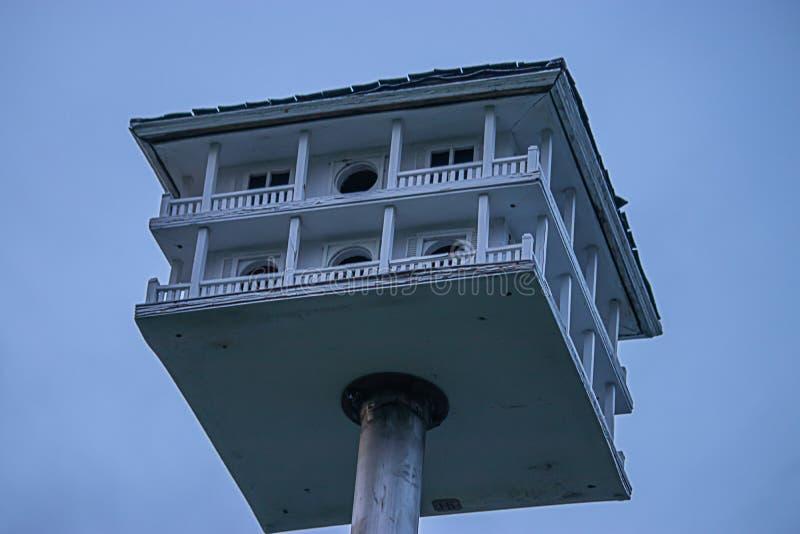 Een oude hand bewerkte vogelhuis met pilars een omslag rond dek en dak op een pool stock afbeeldingen