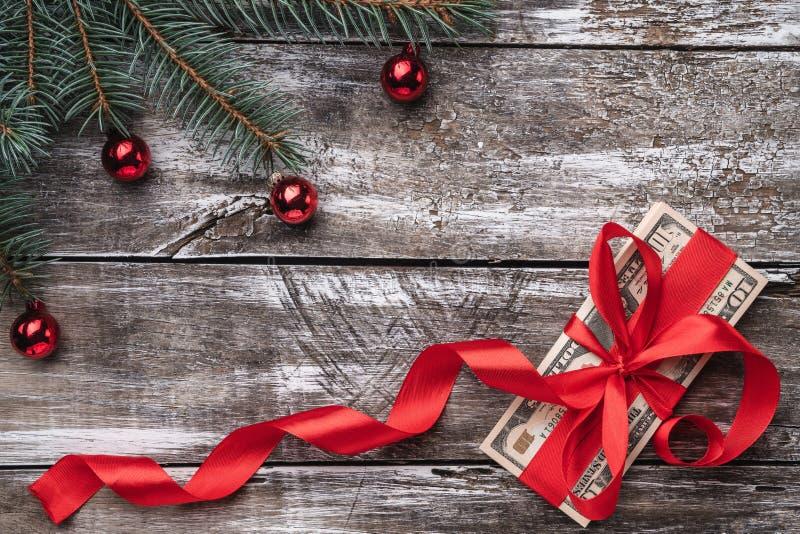 Een oude houten die Kerstmisachtergrond, een spar met snuisterijen, geld met rode verslapping wordt opgesmukt royalty-vrije stock foto's