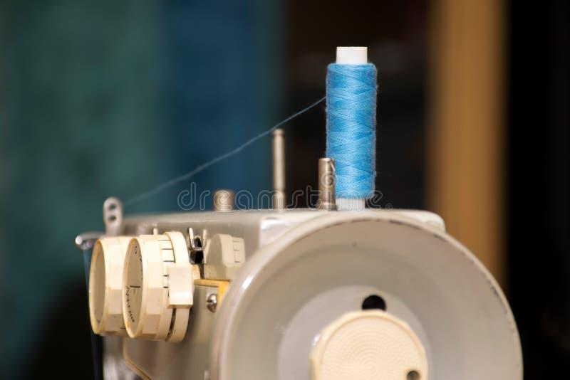 Een oude huishouden naaimachine met een blauwe van de draadrol en olie sporen royalty-vrije stock afbeeldingen