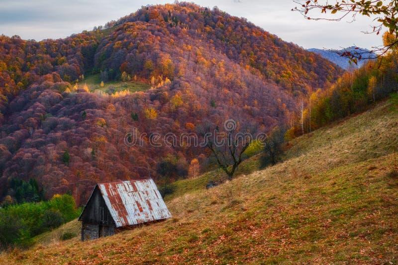Een oude hut in het landschap van de de herfstberg stock afbeelding