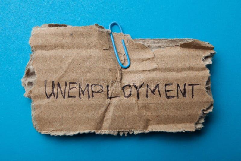 Een oude kartontablet met de inschrijvings 'werkloosheid stock afbeelding