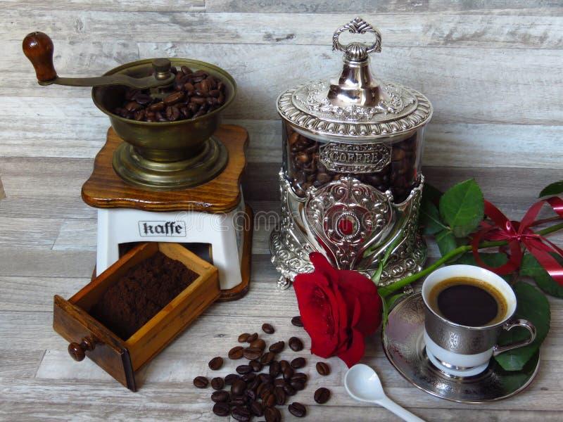 Een oude klassieke koffiemolen, een zilveren koffiekruik, een kop van koffie en een rood namen toe Retro stijl royalty-vrije stock foto