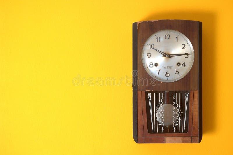 Een oude klok op gele muur royalty-vrije stock afbeeldingen