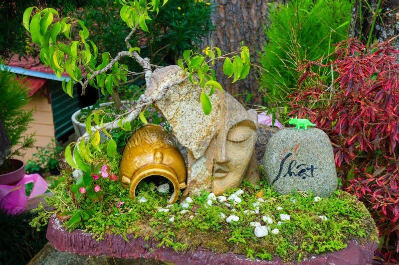 Een oude kruik en een beeldhouwwerk van een gezicht dichtbij de bloemen in het park stock foto