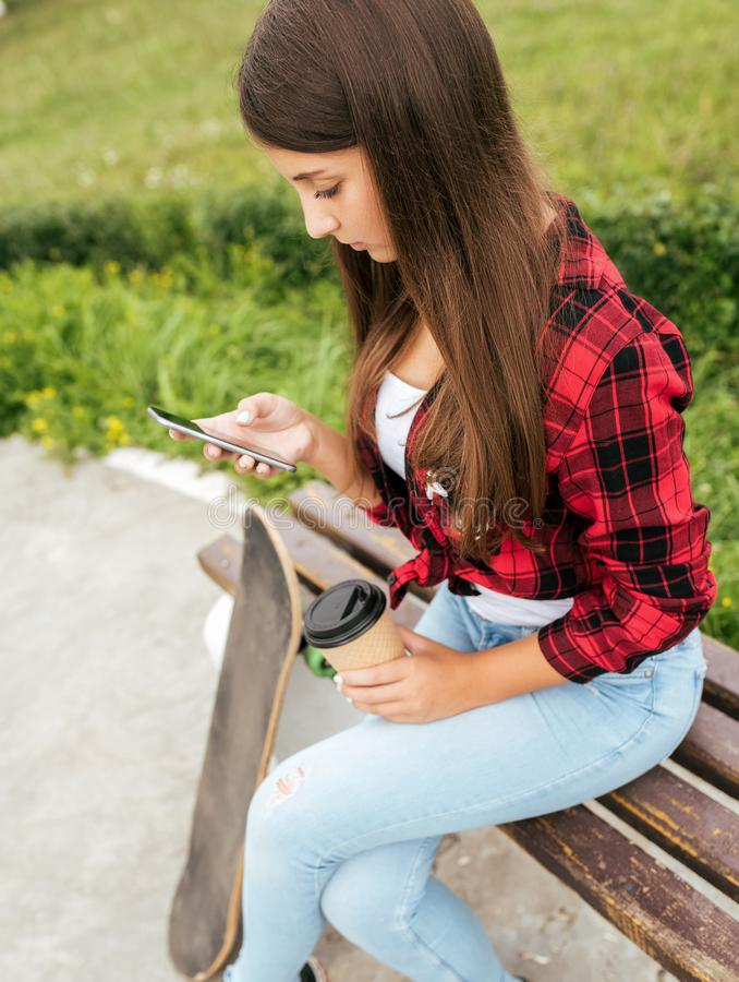 Een oude meisjestiener 10-13 jaar zit op een bank in zijn handen houdend een smartphone en een kop thee Mededeling over stock foto's