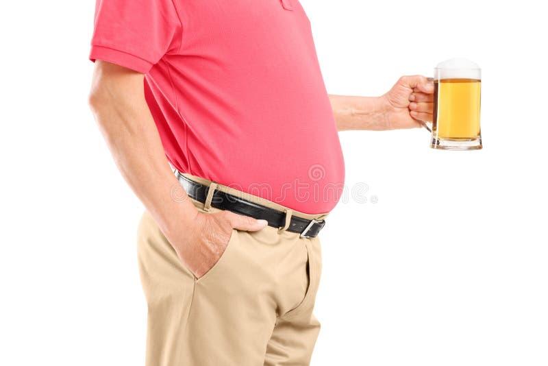 Een oude mens die met buik een bierglas houden stock foto