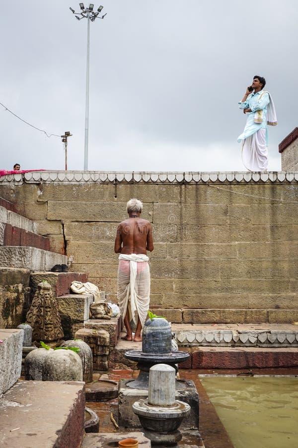 Een oude mens die in Varanasi, India bidden stock afbeeldingen