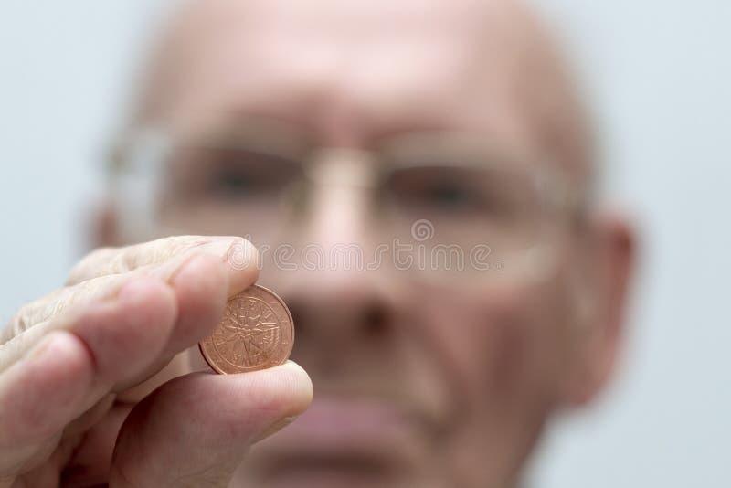 Een oude mens houdt in zijn hand een muntstuk van eurocent twee stock foto