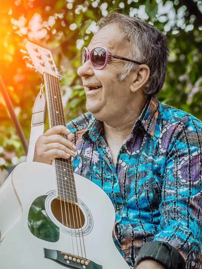 Een oude mens met een gitaar geniet van het leven royalty-vrije stock foto's