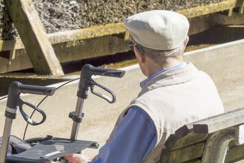 Een oude mens zit op een bank in het park stock afbeelding