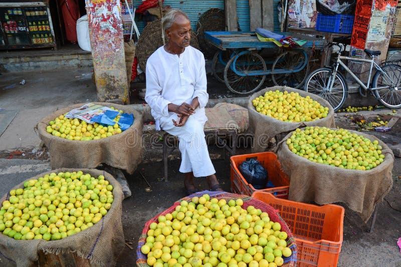 Een oude mensen verkopende vruchten bij de markt in Varanasi, India stock afbeelding