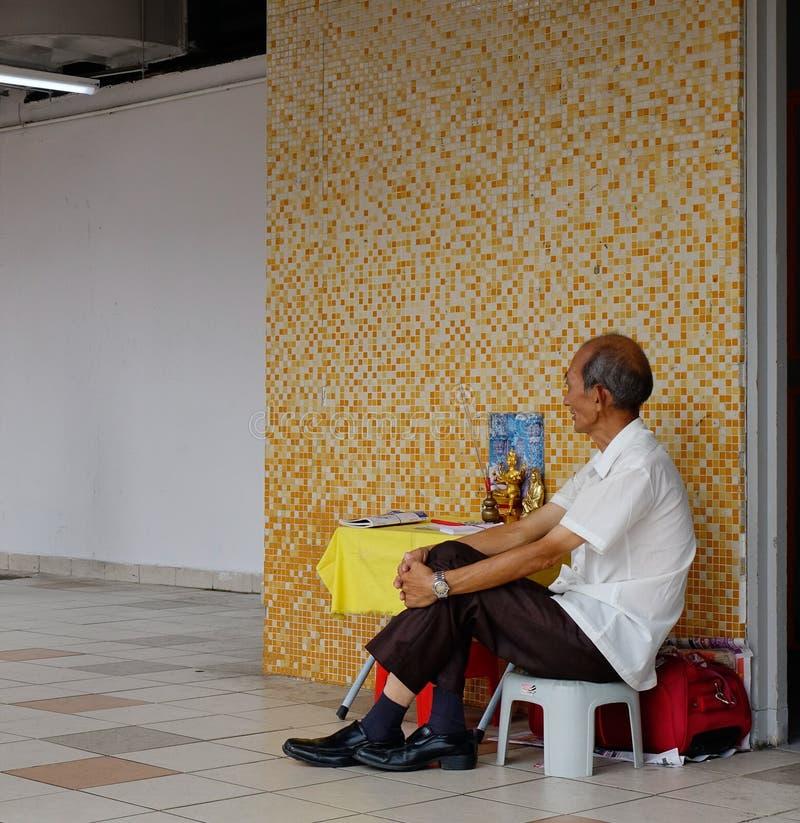 Een oude mensenzitting op straat in Saigon, Vietnam stock afbeeldingen