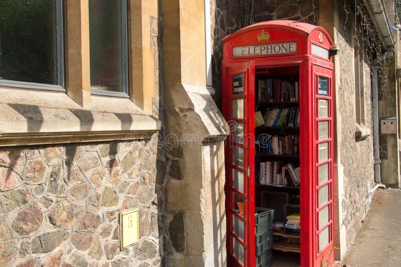 Een oude rode die telefooncel, als communautaire bibliotheek, Malvern, Worcestershire, het UK wordt gebruikt royalty-vrije stock foto's
