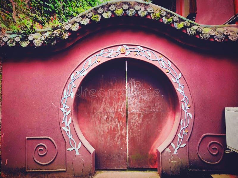 Een oude ronde rode deur stock foto's