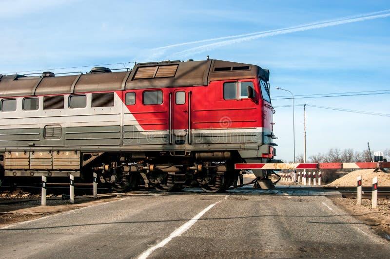 Een oude Russische rode trein die over een spoorwegovergang, op een kleine weg overgaan stock fotografie