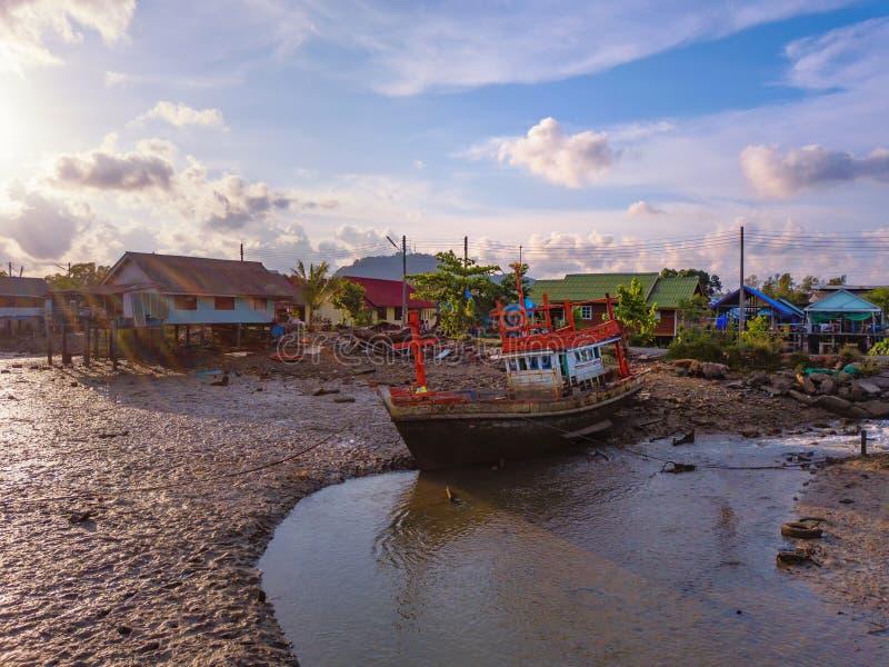 Een oude schipbreuk of een verlaten visserijschip met waterval bij de achtergrond van de zonsonderganghemel in kust van Phuket-St royalty-vrije stock fotografie